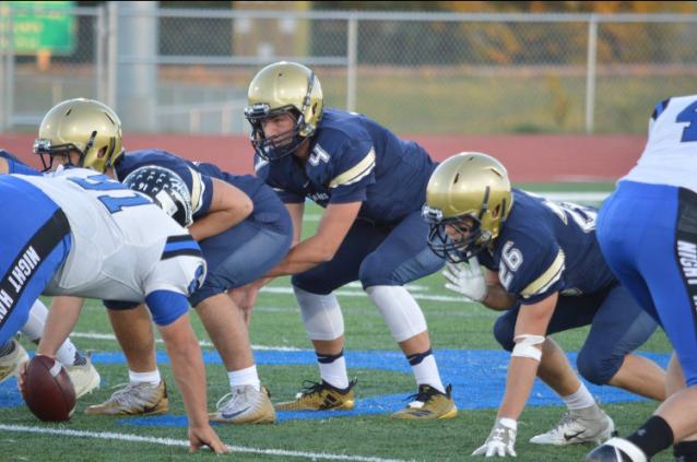 Junior quarterback Jaden Mitzel takes snap against Hettinger defense (Photo courtesy of Tim MItzel)